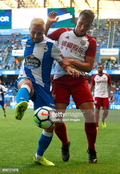 Florin Andone of Deportivo de La Coruna is challenged by Kane Wilson of West Bromwich Albion during the Pre Season Friendly match between Deportivo...