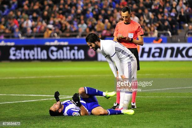 Florin Andone of Deportivo reacts after a tackle as Real Madrid's Isco stands next to him during the Spanish league football match between Deportivo...