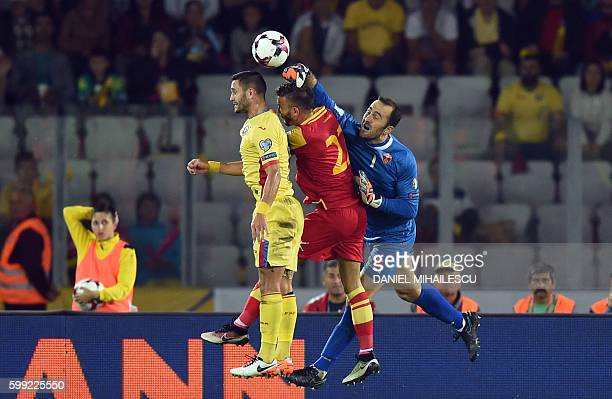 Florin Andone of Romania vies with Marko Simic and goalkeeper Mladen Bozovic of Montenegro during the World Cup 2018 football qualification match...