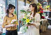 Florist and customer talking and smiling holding flowers in shop