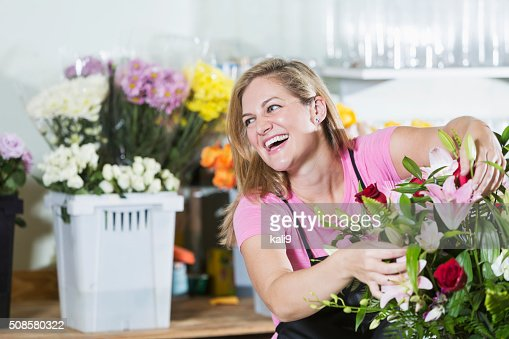 Florist arranging bouquet of flowers in vase : Stock Photo