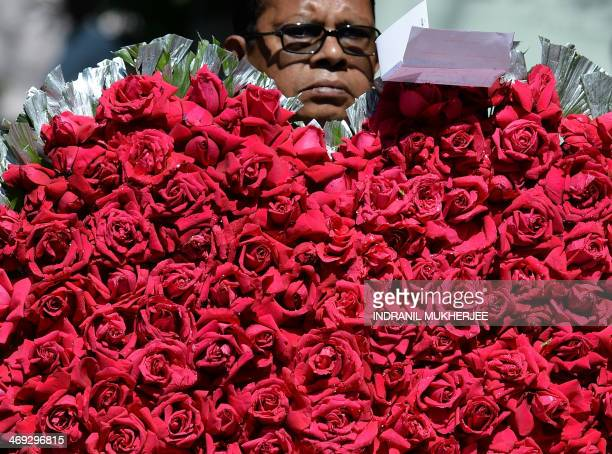 A florist carries a heart shaped flower arrangement made with roses for delivery on Valentine's Day in Mumbai on February 14 2014 Valentine's Day is...