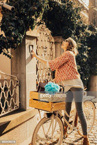Florist girl ringing a bell in front of a client's house