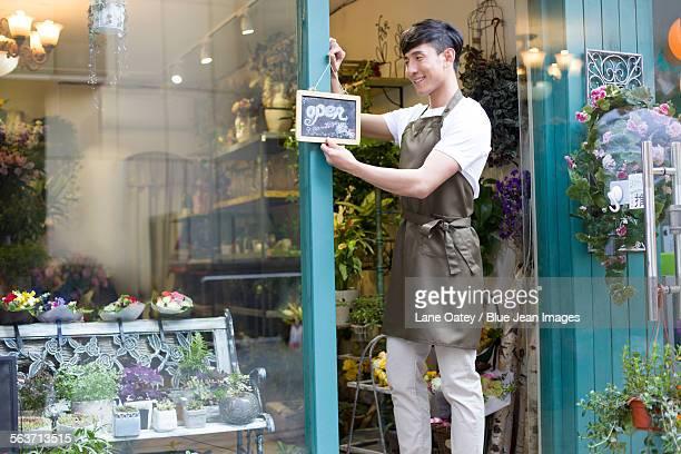 Florist holding an open sign