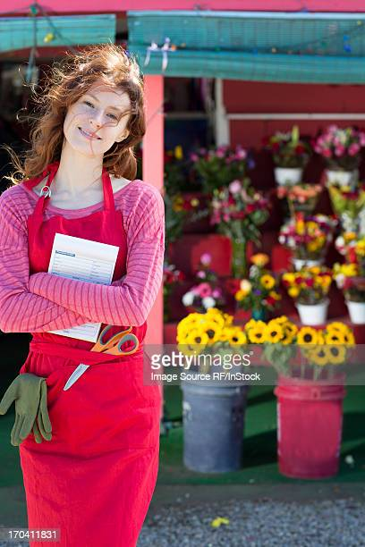 Florist holding notebook in shop