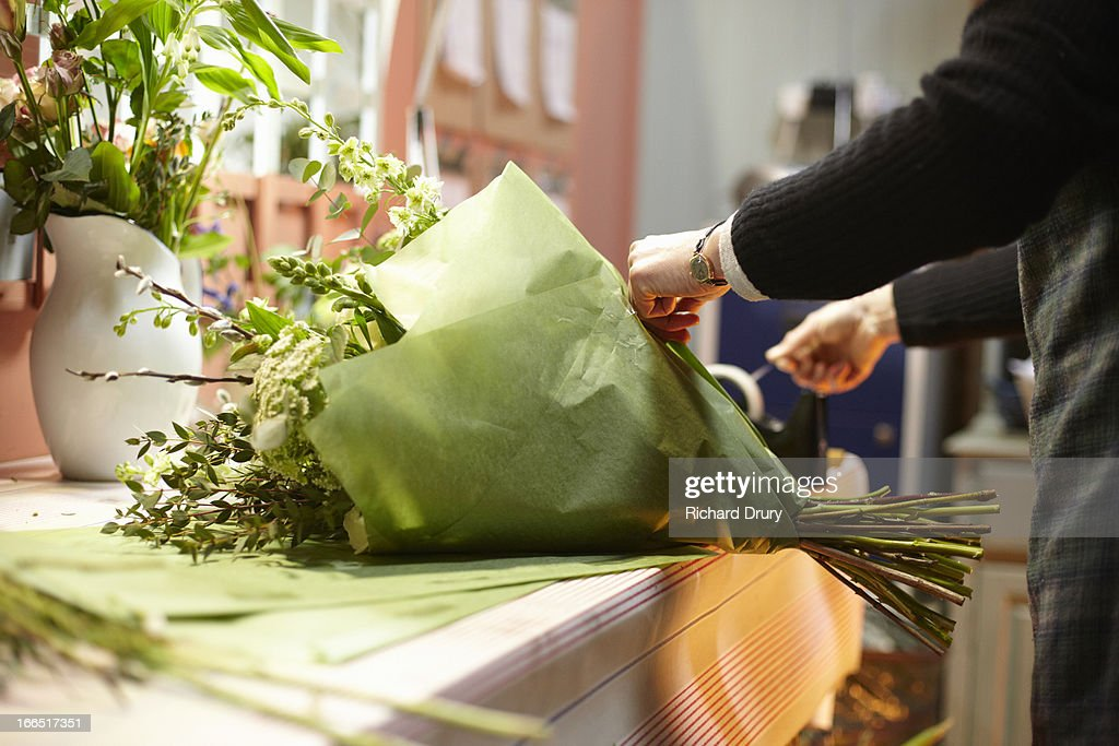 Florist in her shop preparing bouquet of flowers