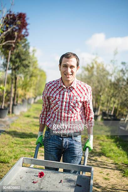 florist owner with wheelbarrow in a plant nursery