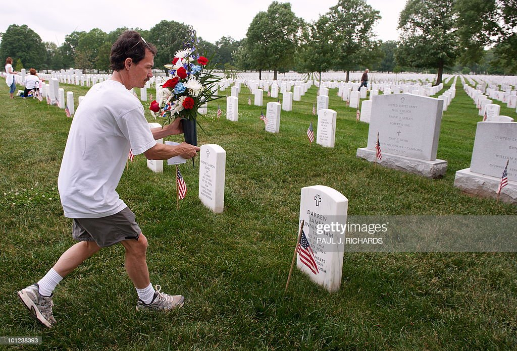 Florist Paul Brockway from Conklyn's Flowers in Arlington, Virginia, races through the gravestones of Arlington National Cemetery on May 28, 2010 delivering flowers ordered for Memorial Day by people who cannot visit the gravesite of a US military member buried at the cemetery. Brockway said he may have delivered 500 seperate arrangements of flowers to gravesites by the end of Memorial Day. AFP PHOTO/Paul J. Richards
