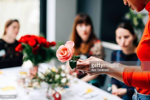 Florist showing rose to students in flower arranging workshop