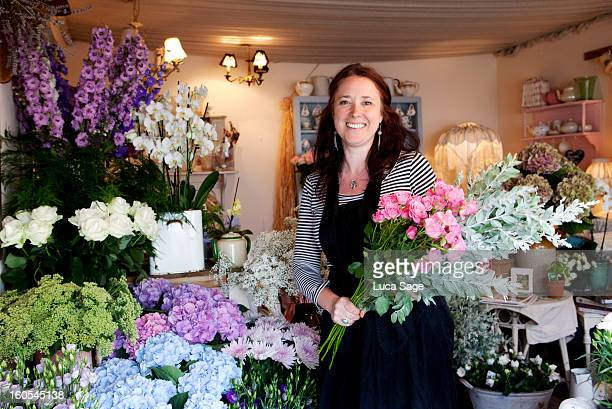 A florist smiles amidst her array of flowers