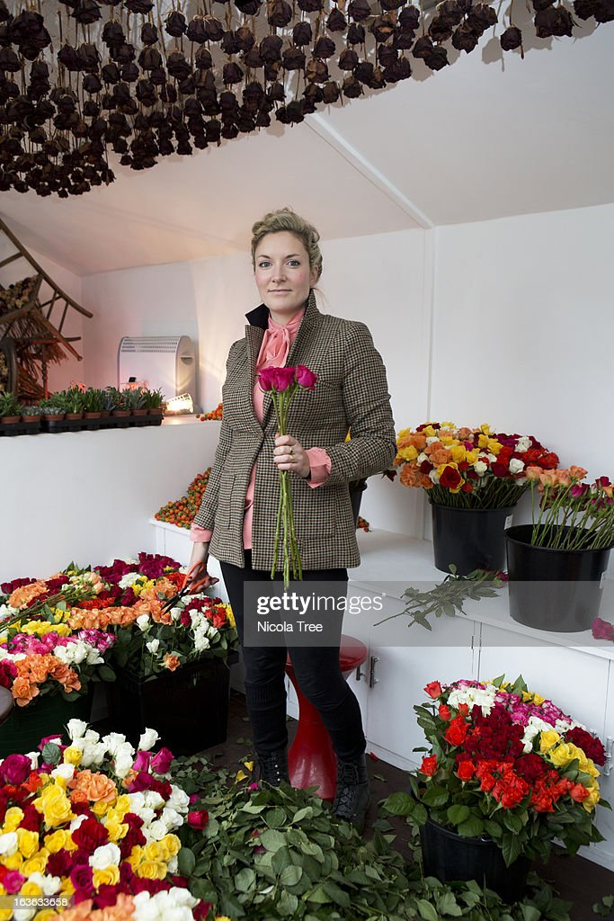 A florist surrounded by flowers in her shop : Stock Photo