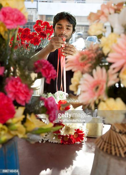 Florist tying a ribbon on a bouquet