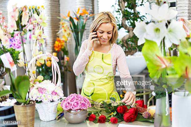 Florist using cell phone in a flower shop.