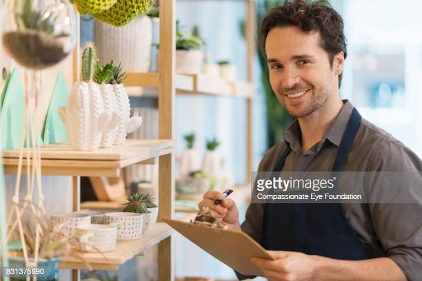 Florist with clipboard in flower shop