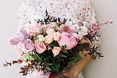 Florist woman holding a beautiful fresh blossoming flower bouquet of peony, roses, lilac, eustoma, mattiola in pink and lavender colors on the grey wall background