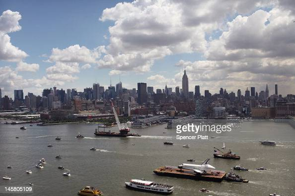 A flotilla surrounds NASA space shuttle Enterprise as it is carried by barge up the Hudson River on route to its permanent home at the Intrepid Sea...