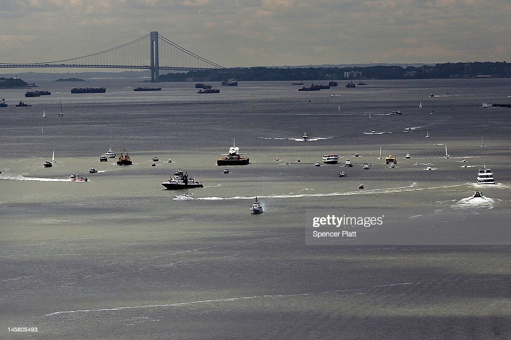 A flotilla surrounds NASA space shuttle Enterprise as it is carried by barge past the Verrazano-Narrows Bridge up the Hudson River on route to its permanent home at the Intrepid Sea, Air and Space Museum on June 06, 2012 in New York City. The Enterprise, only used for atmospheric testing, will be hoisted by crane onto the flight deck of the retired Intrepid aircraft carrier. The Enterprise's original move-in date was Tuesday but bad weather had delayed preparation work.