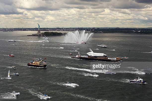 A flotilla surrounds the NASA space shuttle Enterprise as it is carried by barge past the Statue of Liberty up the Hudson River on route to its...