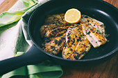 Flounder fillet roasted in a skillet with herbs and lemon butter