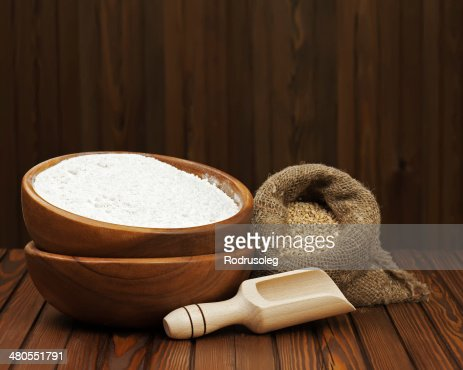 Tazón de madera y harina de trigo en bolsa de arpillera. : Foto de stock