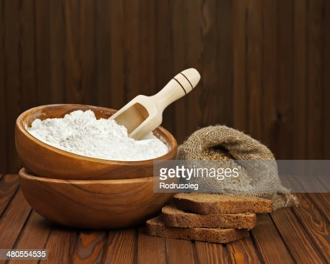 Flour in wooden bowl and wheat in burlap bag. : Stock Photo