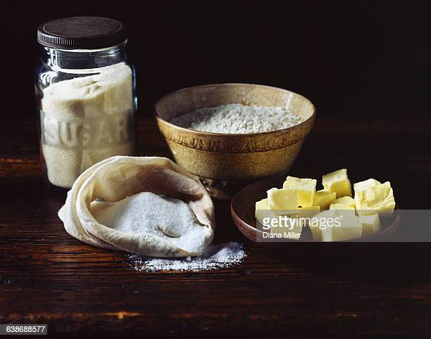 Flour, sugar and butter on wooden surface