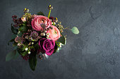 Flower arangement of roses and ranunculus on black concrete background.  Greeting card concept, copy space for text