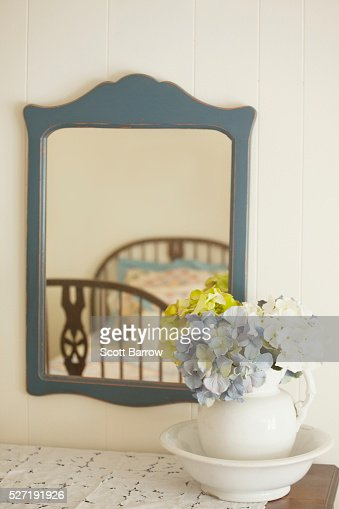 Flower arrangement on dresser beside mirror : Stock-Foto
