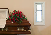 Flower arrangements on top of open coffin