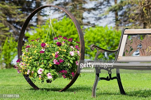 Flower Basket Hanging on Wagon Wheel by Garden Bench : Stock Photo