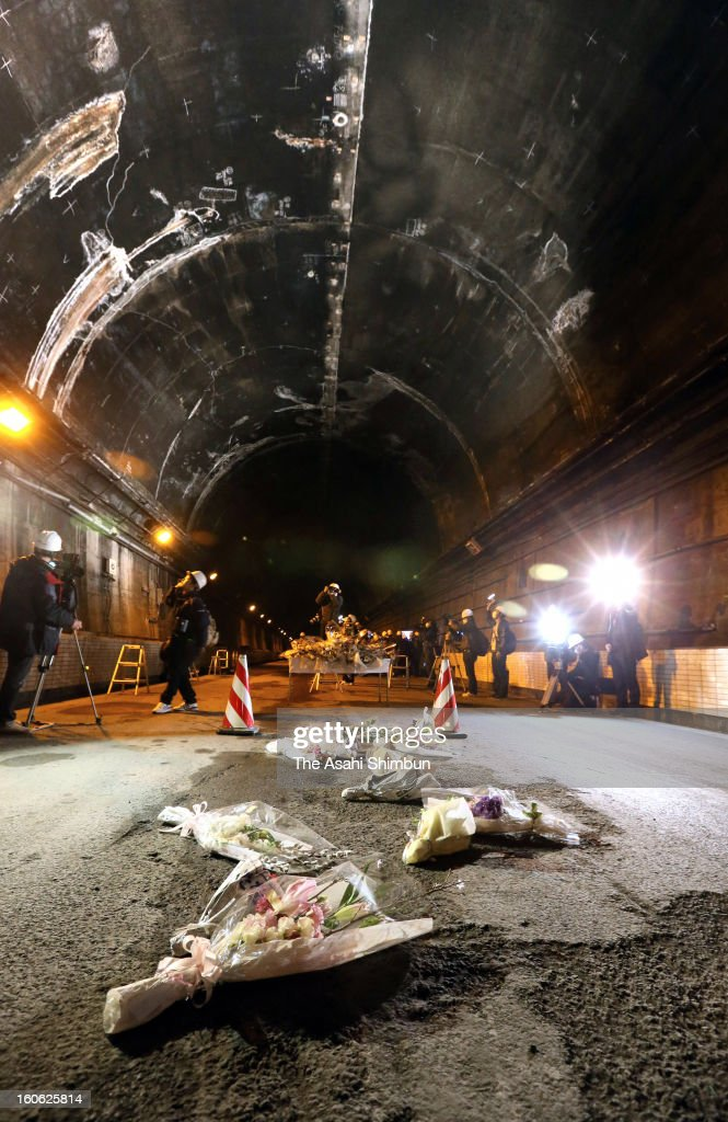Flower bunches offered by the relatives of the victims lie on the road at the accident site of Sasago Tunnel on February 3, 2013 in Otsuki, Yamanashi, Japan. The concrete ceiling panels of the tunnel collapsed over 130 metres, three cars were involved and killed 9 people at December 2 accident.