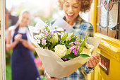 A young woman stands at the front door of her home and reads the card from a big bouquet of flowers . Behind her is the delivery girl who has just dropped them off. The shallow focus is on the bouquet