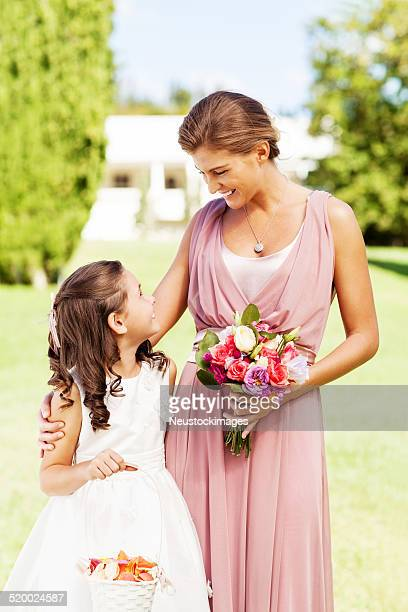 Flower Girl And Bridesmaid Looking At Each Other During Wedding