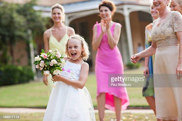 Flower girl holding bouquet at wedding reception