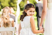 Portrait of flower girl looking over shoulder holding bride's hand during outdoor wedding. Horizontal shot.