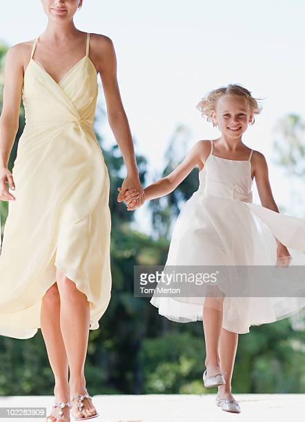 Flower girl holding hands with mother
