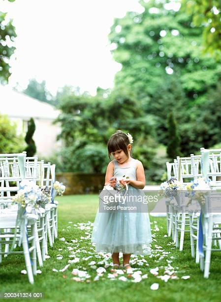 Flower girl (3-5) scattering flower petals down aisle