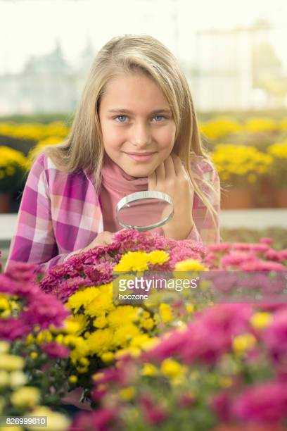 Flower girl using magnifying glass in greenhouse