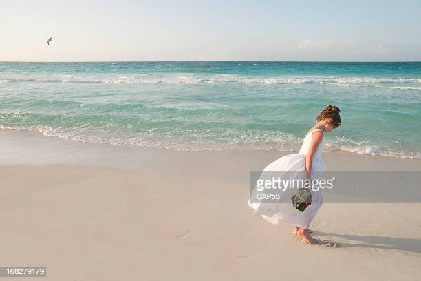 Flower Girl Walking On The Beach During Wedding Day