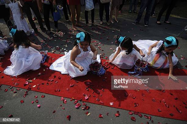 Flower girls collect rose petals scattered on the carpet during a mass wedding ceremony on Valentine's day in Manila Philippines February 14 2014 The...