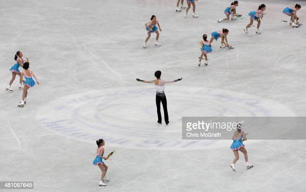 Flower girls rush to clear the ice as Yuzuru Hanyu of Japan salutes the crowd after finishing his routine in the Men's Free Skating during ISU World...