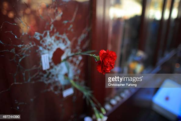 A flower is placed inside a bullet hole in the window of Le Carillon restaurant as France observes three days of national mourning for the victims of...