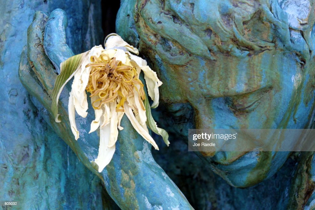 A flower is placed into the hand of a statue, by artist Kenneth Treister, which is part of a sculpture depicting thousands of victims crawling into an open hand representing freedom April 29, 2001 at the Holocaust Memorial in South Beach, FL.