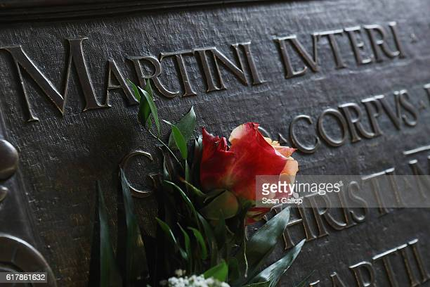 A flower lies next to an inscription on the tomb of Martin Luther in the Schlosskirche church which is the same church where in 1517 Luther nailed...