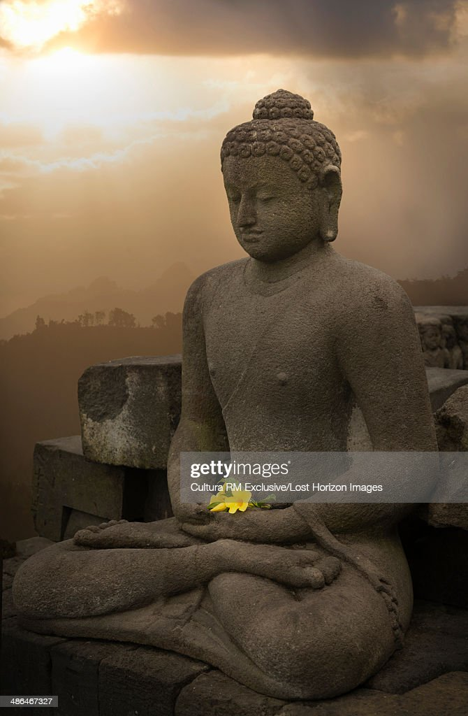 Flower offering and buddha, The Buddhist Temple of Borobudur, Java, Indonesia : Stock Photo
