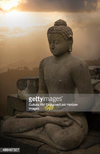 Flower offering and buddha, The Buddhist Temple of Borobudur, Java, Indonesia : Stock Photo