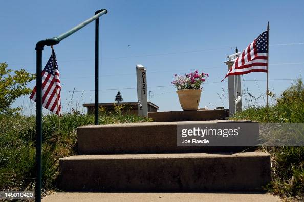 A flower pot and flowers are seen on what used to be the stairway leading to a home before it was destroyed one year ago today when the town was hit...