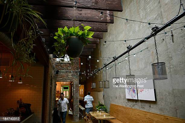 Flower pots hang from the ceiling at Rose's Luxury a new restaurant on 8th Street in Southeast which offers spicy pork and lychees and brisket for...