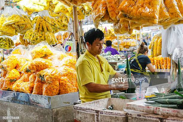 A flower seller prepares flowers for New Year's Eve at the Pak Khlong Talat on December 31 2015 in Bangkok Thailand