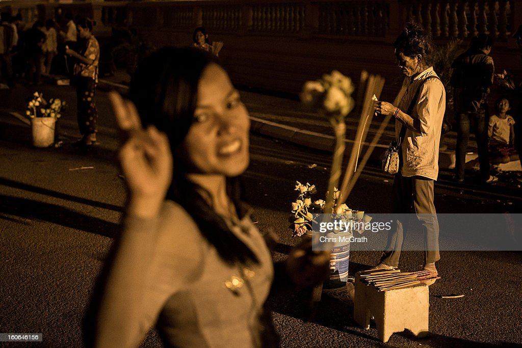 Flower sellers work the street as a woman poses for a photograph outside the Royal Palace after the cremation ceremony for former King Norodom Sihanouk on February 4, 2013 in Phnom Penh, Cambodia. The former King's cremation ceremony comes on the fourth day of a seven day royal funeral ceremony and nearly four months since his death in Beijing last October. Foreign leaders from 16 countries attended the cremation ceremony.